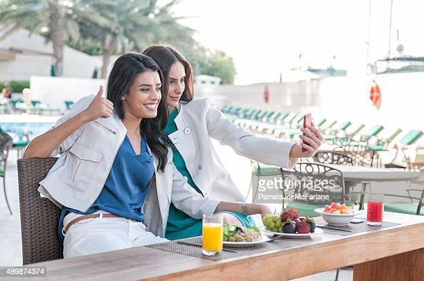 Middle Eastern Women Taking Selfie, Poolside Café, Luxury Hotel, Dubai.