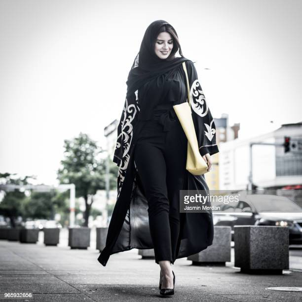 Middle Eastern young woman walking on street in city