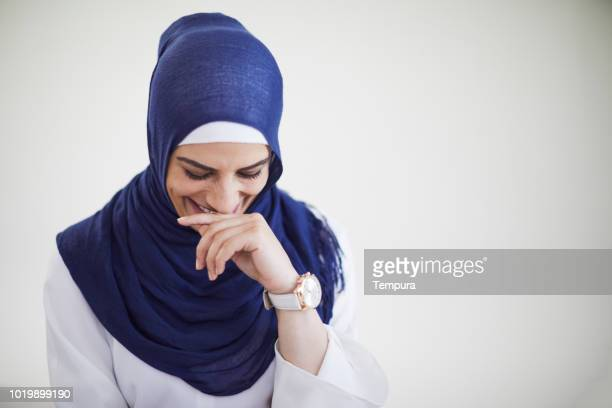 middle easterner woman wearing a  hijab looking shyly away from camera. - shy stock pictures, royalty-free photos & images
