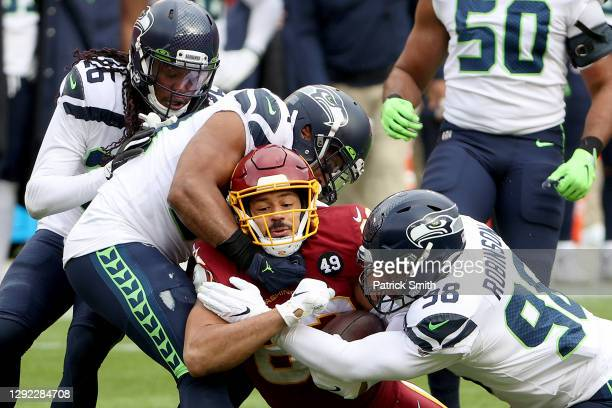 Middle linebacker Bobby Wagner and defensive end Alton Robinson of the Seattle Seahawks tackle tight end Logan Thomas of the Washington Football Team...