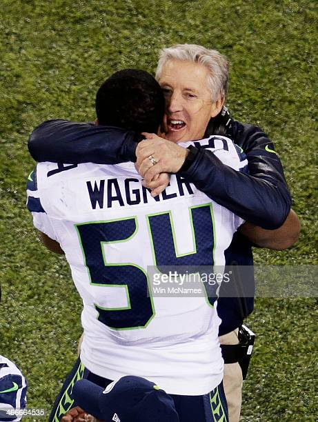 Middle linebacker Bobby Wagner and head coach Pete Carroll of the Seattle Seahawks embrace after their 43 to 8 win over the Denver Broncos during...