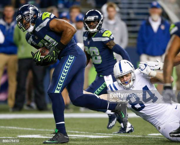 Middle linebacker Bobby Wagner of the Seattle Seahawks makes a fumble recovery for a touchdown against tight end Jack Doyle of the Indianapolis Colts...