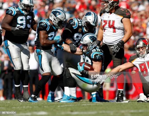 Middle linebacker Luke Kuechly of the Carolina Panthers is helped up by strong safety Mike Adams of the Carolina Panthers after intercepting a pass...
