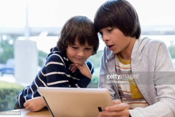 middle school boy teaches brother how to use laptop - children only stock pictures, royalty-free photos & images