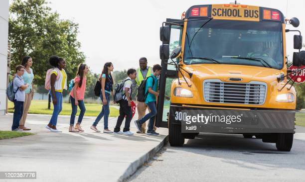 middle school class boarding bus, boy with down syndrome - school bus stock pictures, royalty-free photos & images
