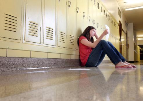 Middle school girl looking at classwork - gettyimageskorea