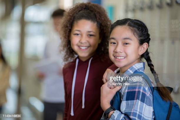 middle school girls smiling in corridor - junior high student stock pictures, royalty-free photos & images