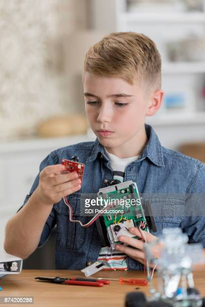 Middle school student attaches component to robot