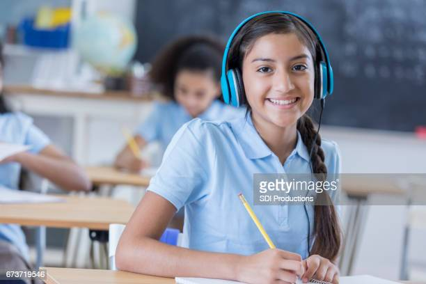 Middle school student listens to headphones during class