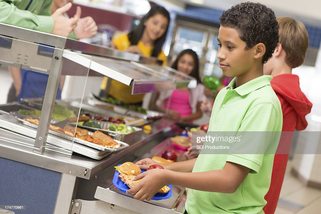 Middle school students getting lunch items in cafeteria line : Stock Photo