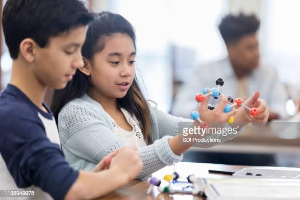 los estudiantes de secundaria estudian el modelo de estructura molecular - átomo fotografías e imágenes de stock
