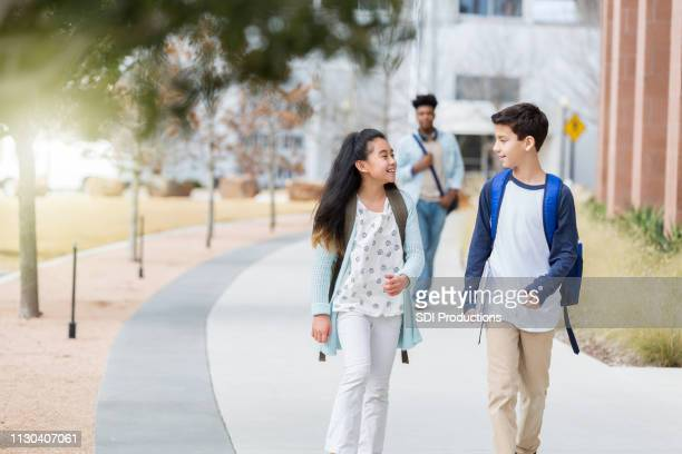 middle school students walking on campus - junior high student stock pictures, royalty-free photos & images