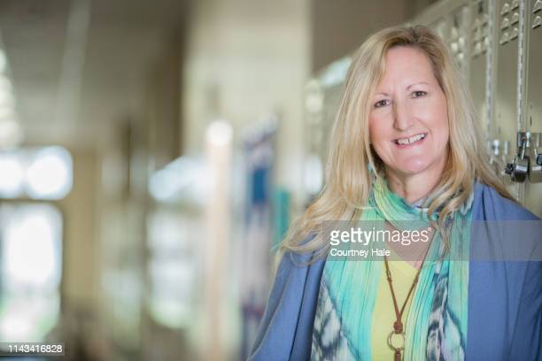 middle school teacher standing in corridor - charter_school stock pictures, royalty-free photos & images