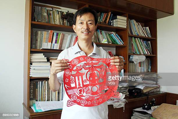 Middle school teacher Zhang Weiyong shows his paper cut of Hangzhou city on August 25 2016 in Tonglu County Hangzhou City Zhejiang Province of China...