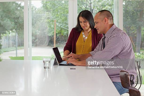 middle-adult woman and man looking at tablet - vcg stock pictures, royalty-free photos & images