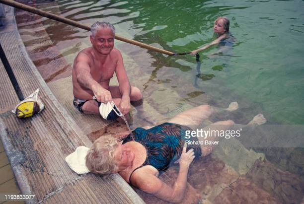 A middleage husband pours thermal healing spa waters on to his wife in Budapest's famous Szechenyi thermal bath on 18th June 1990 in Budapest Hungary...