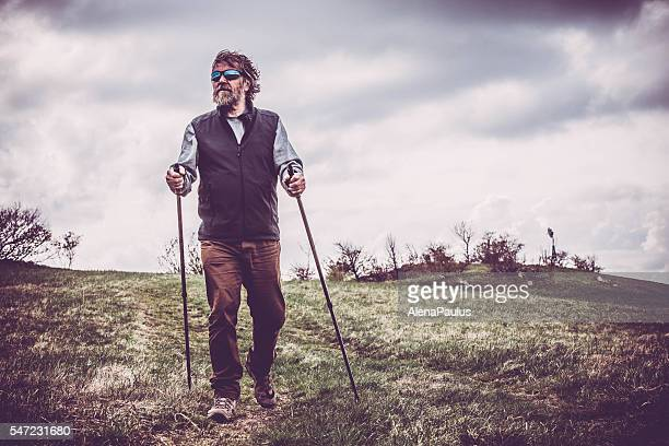 Middle-age man exercising with a Nordic walking technique