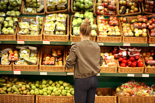 Middle-age woman buying vegetables at the market 985954662