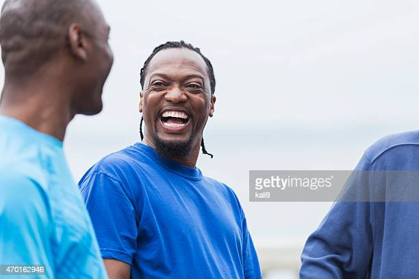Middle-aged African American man laughing with friends