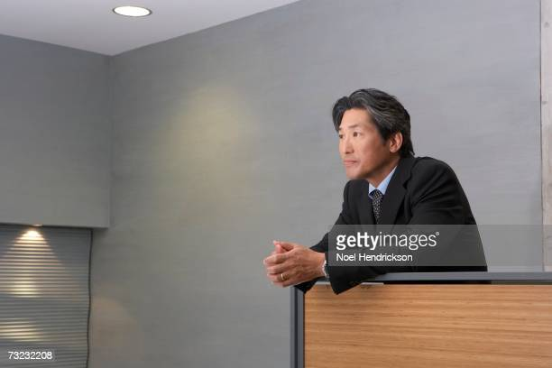 Middle-aged Asian businessman leaning on railing indoors
