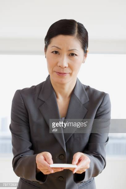 Middle-aged Asian businesswoman offering business card