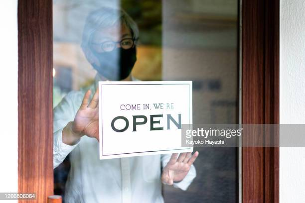 a middle-aged asian man puts up a sign in a storefront announcing the reopening of business. - store opening stock pictures, royalty-free photos & images