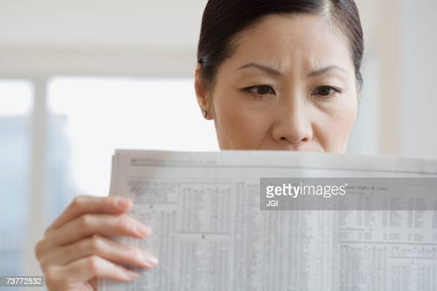 Middle-aged Asian woman reading newspaper