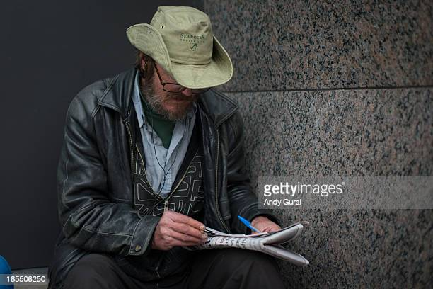 Middle-aged bearded man seated outdoors near a granite wall has a folded newspaper on his knee and is about to start the puzzle. His face is obscured...