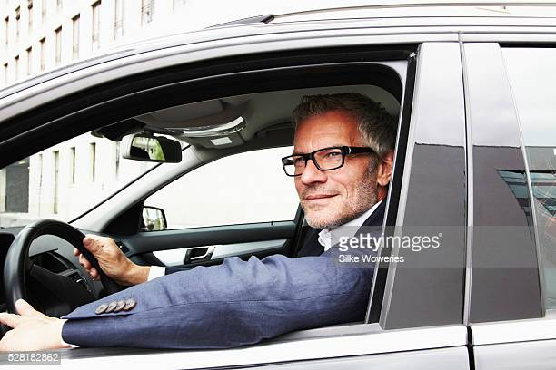 Middle-aged businessman driving car