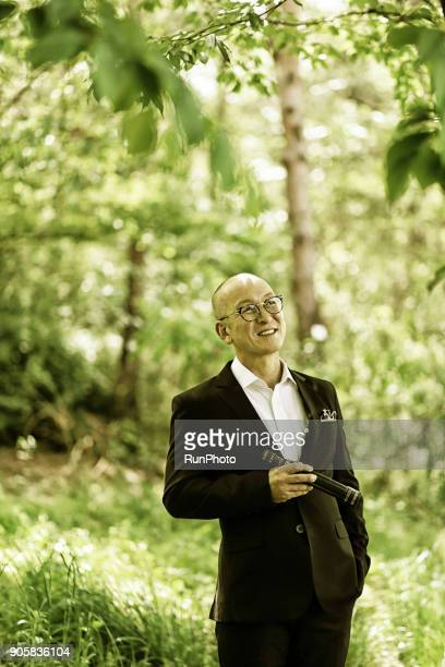 middle-aged businessman in the forest with a telescope