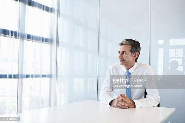Middle-aged businessman sitting in office and looking through window