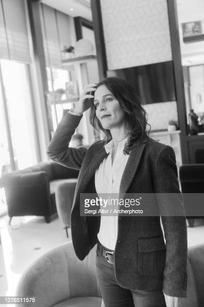 middle-aged businesswoman in black and white with hand in her hair - sergi albir fotografías e imágenes de stock