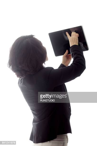 Middle-aged businesswoman using digital tablet