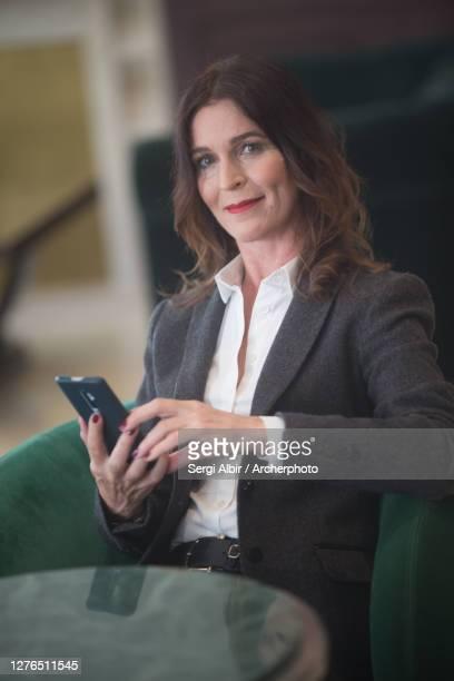 middle-aged businesswoman with mobile phone - sergi albir fotografías e imágenes de stock