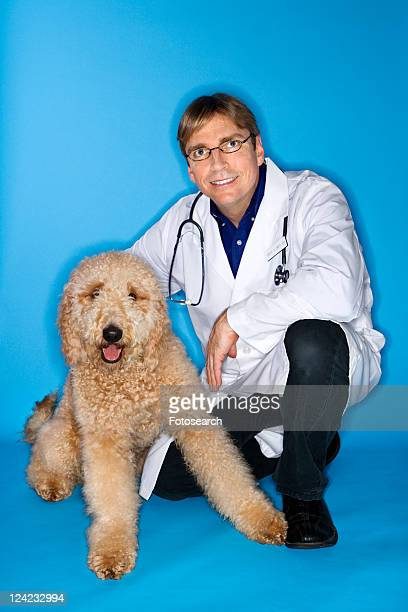 Middle-aged Caucasian male veterinarian with Goldendoodle dog.