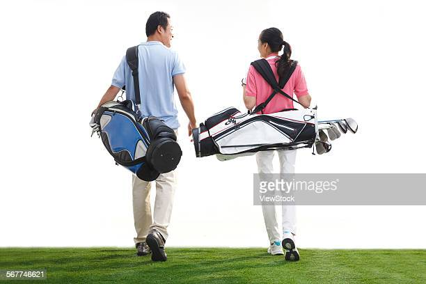 A middle-aged couple carrying golf bag