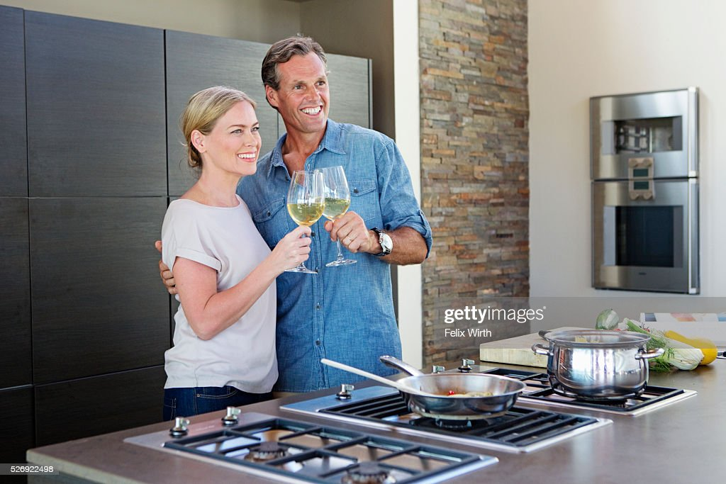 Middle-aged couple cooking together and drinking wine : Bildbanksbilder