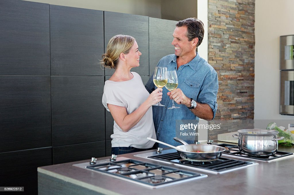 Middle-aged couple cooking together and drinking wine : Foto de stock
