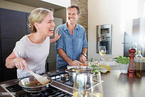 middle-aged couple cooking together - 45 49 years stock pictures, royalty-free photos & images