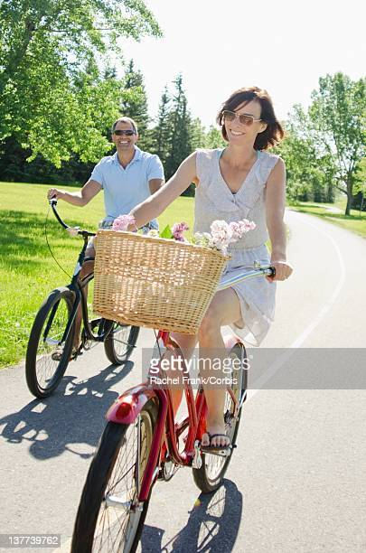 Middle-aged couple cycling in park