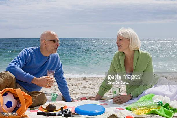 Middle-aged couple relaxing on beach
