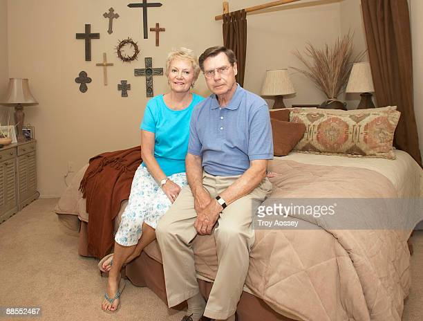 Middle-aged couple sitting in bedroom with crosses