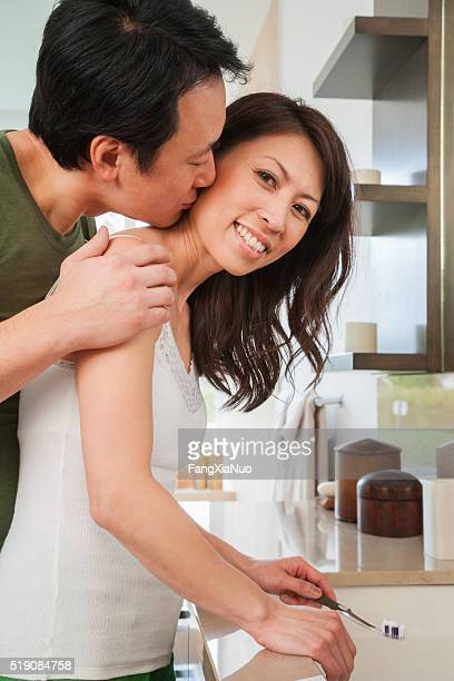 middle-aged couple snuggling in bathroom - couple and kiss and bathroom stock photos and pictures