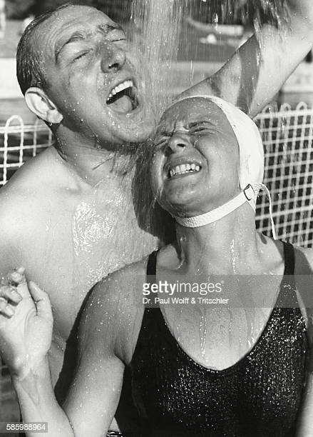 Middleaged couple taking a shower in an openair swimming pool