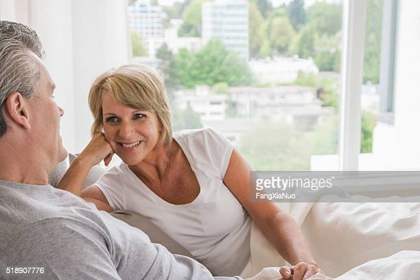 Middle-aged couple talking in bed