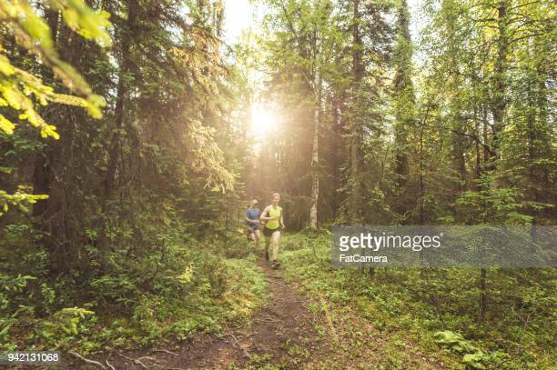 Middle-aged couple trail running in the forest