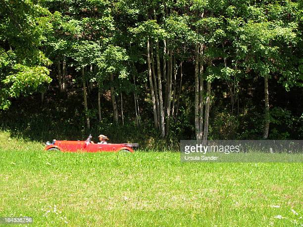 CONTENT] Middleaged couple with summer hats on their heads makes a trip in open red vintage car on a country road through the green summer landscape...