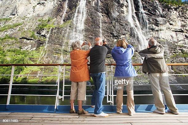middle-aged couples photographing a waterfall - fanny pic stock photos and pictures