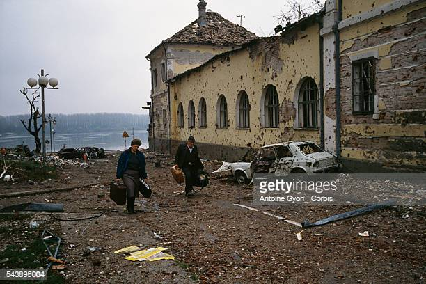 A middleaged Croatian couple flees the ruined city of Vukovar past bombed buildings riddled with bullet holes and streets filled with rubble after a...