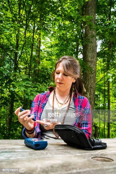 Frau mittleren Alters Diabetes kontrollieren ihren Blutzucker außerhalb auf einem Deck.